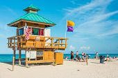 MIAMI,USA - MAY 26,2014 : People enjoying the beach near an iconic lifeguard tower in South Beach on