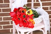 Bouquet of colorful tulips in wicker basket, on chair, on home interior background