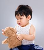 Cute baby boy play with doll
