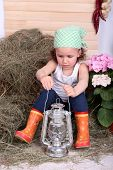Beautiful small girl holding kerosene lamp on country style background