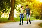 couple ride rollerblades in the park