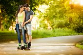 Love couple ride rollerblades in the park, spending time together