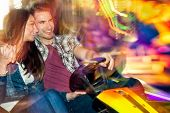 Young couple in love in a bumper car / dodgem ride, having fun in amusement park