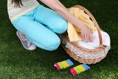 Woman holding laundry basket with clean clothes, towels and pins, on green grass background
