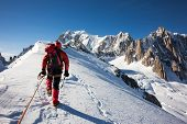 Mountaneer climbs a snowy ridge in Mont Blanc, France. Enterprise, diligence, team work: mountaneeri