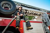 Firefighter sitting on a firefighting truck with water hose