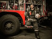 stock photo of firefighter  - Cheerful firefighter near truck with equipment - JPG