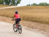 Woman Cyclist Riding On The Road