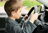 stock photo of rudder  - boy driving a car and looking at the way horizontal - JPG