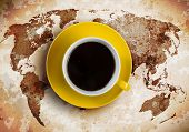 Cup of coffee with world map at background