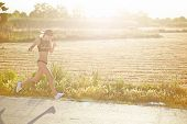 Female runner jogging along a road through the sun's rays