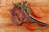 savory : roasted beef spare rib on wooden plate with cutlery and thyme isolated over white backgroun
