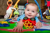 picture of playmates  - Happy and curious infant baby boy playing on activity mat - JPG