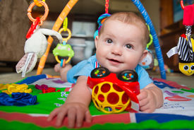 foto of playmate  - Happy and curious infant baby boy playing on activity mat - JPG