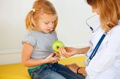 Doctor Giving Green Apple To Small Patient.