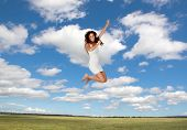 Attractive young woman jumping on a beautiful landscape with a blue sky