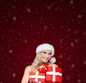Beautiful girl in Christmas cap holds a set of gifts wrapped with red paper, isolated on purple
