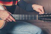 Man Tuning Guitar