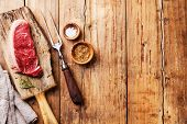 Raw Fresh Meat Striploin Steak And Meat Fork On Wooden Background