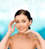 beauty, people and health concept - smiling young woman with bare shoulders over blue glass background