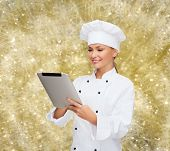 cooking, holidays, technology and people concept - smiling female chef, cook or baker with tablet pc computer over yellow lights background
