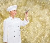 cooking, holidays, advertisement and people concept - smiling female chef, cook or baker with marker writing something on virtual screen over yellow lights background