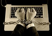 picture of slave  - Hands of caucasian businessman addicted to work tied and bond with iron chain handcuffed to computer laptop in workaholic internet slave and addict concept in black and white - JPG