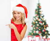 winter holidays, christmas, advertising and people concept - smiling young woman in santa helper hat with white blank billboard over living room with christmas tree background