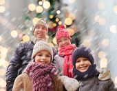 family, childhood, season, holidays and people concept - happy family in winter clothes over christmas tree lights background