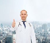 healthcare, profession, gesture and medicine concept - smiling male doctor with stethoscope showing thumbs up over city background