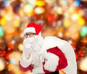christmas, holidays and people concept - man in costume of santa claus with bag making hush gesture over red lights background