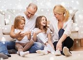 family, childhood, people and home concept - smiling parents with two little girls sitting on floor at home
