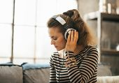 Portrait Of Young Woman Listening Music In Headphones In Loft Ap