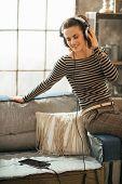 Happy Young Woman Listening Music In Headphones In Loft Apartmen