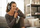 pic of singing  - Portrait of happy young woman singing with microphone in loft apartment - JPG