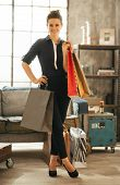 Full Length Portrait Of Happy Young Woman With Shopping Bags In Loft Apartment