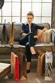 Young Woman With Shopping Bags Sitting In Loft Apartment