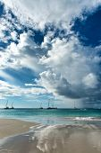 Dramatic clouds over Anse Lazio beach, Seychelles, reflected on the wet sand below with yachts moored offshore in the background