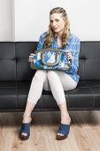 stock photo of clog  - woman wearing denim clogs with a handbag sitting on sofa - JPG