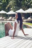Smiling Indian Woman in White Shirt and Shorts with Long Black Hair Relaxing at the Poolside While Looking at the Camera.