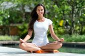 Pretty Smiling Young Woman in White Casual Clothing Doing Lotus Yoga Pose at the Poolside While Looking at the Camera.