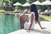 Long Hair Slim Asian Indian Woman Unwinding at Poolside on One Sunny Day.