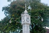 Famous Vintage District Clock Tower in Victoria, Seychelles with Flowering Tall Tree at the Background.