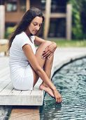 Close up Attractive Young Woman in White Shirt and Shorts Sitting on Wooden Platform at the Pool Side with Hand and Feet Touching the Water.