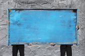 Two Businessman Holding Old Blue Empty Wooden Noticeboard