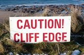 Red Caution Sign On Slippery Cliff Edge