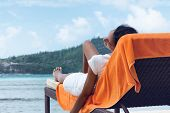 Asian Indian Woman Relaxing on Beach Chair with Towel at the Beachfront.