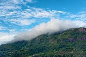 Morne Seychellois, the highest mountain peak on Mahe, Seychelles, blanketed in low lying cloud cover under a cloudy blue sky