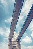 View from below of the arch on the Tower Bridge in London with detail of the external historical stone facade of one of the Towers against a cloudy blue sky