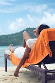 Woman Resting on Sun Lounger with Orange Towel at the Beach During her Vacation Trip.